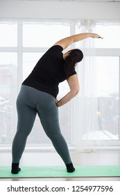 weight loss, healthy lifestyle, sport, activity concept. young overweight woman in sportswear doing yoga exercises at yoga studio