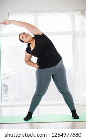 weight loss, healthy lifestyle, sport, activity concept. young overweight woman in sportswear doing stretching exercises to warm up muscles
