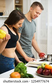 weight loss, keto, detox, paleo diet food, slimming and healthy lifestyle. fit slim couple reading recipe book before cooking