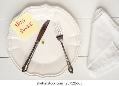 Weight loss new year's concept - single pea on a plate with This Sucks note