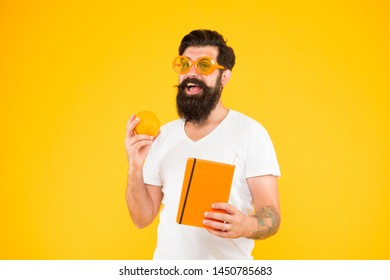 Weight loss and nutrition literature. Bearded man holding orange fruit and book for literature reading on yellow background. Dieting literature information. Literature on healthy diet and nutrition.