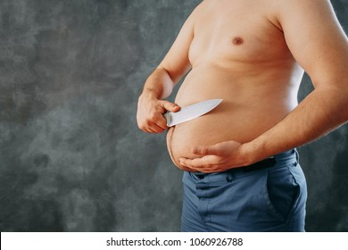Weight loss, overweight, dieting, plastic surgery, liposuction concept. Unknown man trying to cut off fat from his obese belly