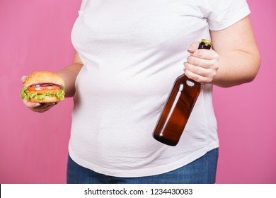 weight loss, overweight, plus size, diet, unhealthy eating, party, alcohol addiction. fat woman with bottle of beer and hamburger