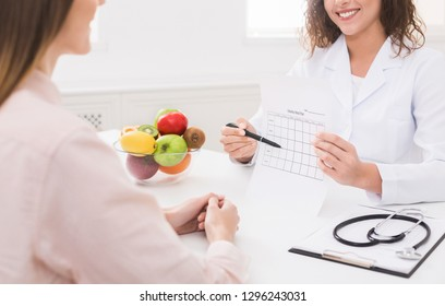 Weight loss program. Healthy nutrition expert making weekly meal plan for client, copy space - Shutterstock ID 1296243031