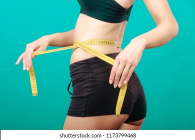 Weight loss, slim body, healthy lifestyle concept. Fit fitness girl measuring her waistline with measure tape on green