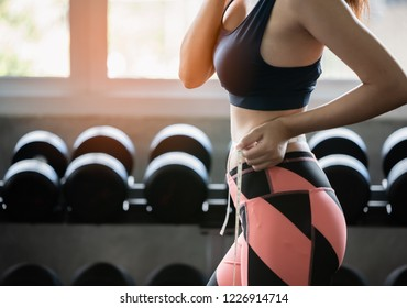 Weight loss, slim body, healthy lifestyle concept. fitness girl measuring her waistline with measure tape in the fitness ,selective focus,healthy concept,copy space.
