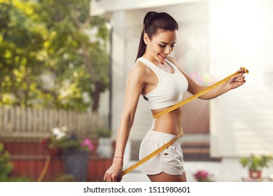 Weight loss, slim body, healthy lifestyle concept. Fit fitness girl measuring her waistline with measure tape
