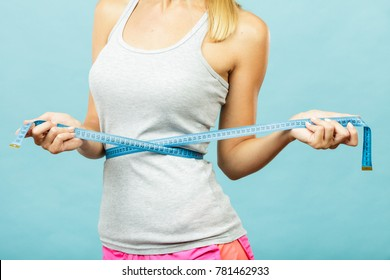 Weight loss, slim body, healthy lifestyle concept. Fit fitness girl measuring her waistline with measure tape on blue