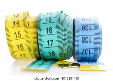 Weight loss and sport concept. Yellow and blue rolled tapes isolated on white background. Three rolled centimeter rulers. Tapes for measuring waist and figure with indicators in form of centimeters.