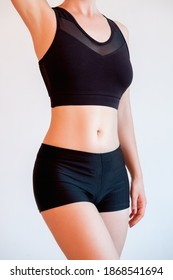 Weight loss. Sport lifestyle. Healthy nutrition. Female activewear. Woman slim body with thin waist in black bra top shorts isolated on neutral background.