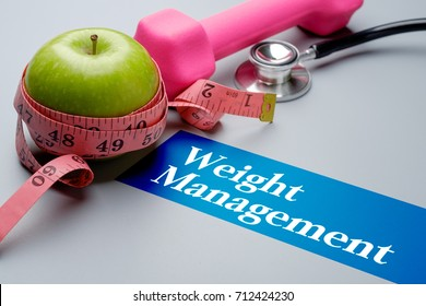 Weight management, health concept. Stethoscope, apple, measuring tape and dumbbell on grey background. Selective focus image.