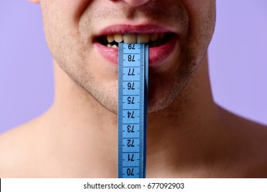 Weight management idea. Male holds blue measuring tape with his teeth. Fitness, regime and diet concept. Guy with flexible ruler in mouth on light purple background, close up