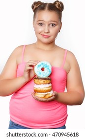 Weight problem - fat funny girl hungry eating donuts. Overweight child need diet. Unhealthy food and plus size kid isolated in studio
