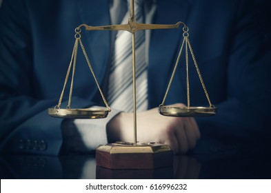 Weight scale of justice, lawyer in background. lawyer law justice judge scales courtroom legal scale concept