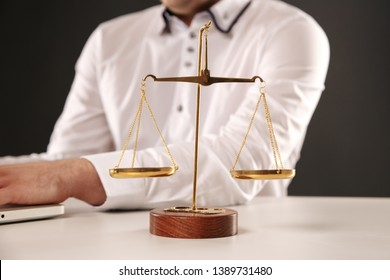 Weight scale of justice and man's hands on the background.