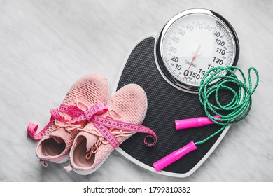 Weight scales with measuring tape, sport shoes and jumping rope on light background. Slimming concept