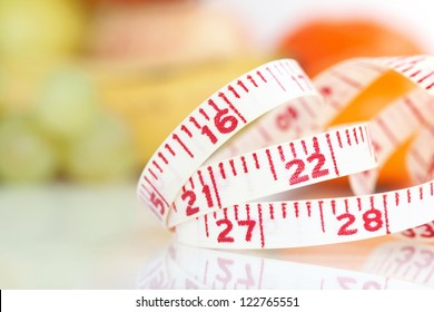 Weight watcher - Measuring tape with different fruits at the background (V-Format ID 174374312)