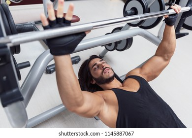 Weightlifter or bodybuilder lying on a bench starting lifting a barbell weight in a gym during training in a healthy active lifestyle and fitness concept