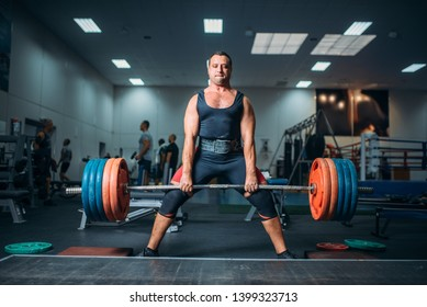 Weightlifter doing exercise with barbell, deadlift