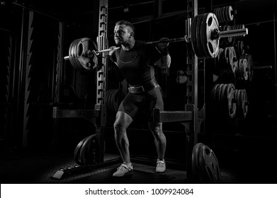 The weightlifter is preparing to lift a very heavy barbell. He exhales breathlessly and strains as much as possible before performing the exercise.