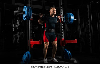 The weightlifter stands with a very heavy barbell on his shoulders. He is at the top and is preparing to sit down.