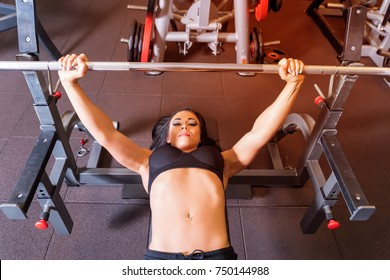 A weightlifting young woman exercising in the gym.