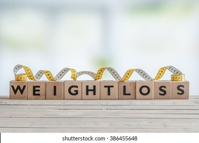 Weightloss sign with measure tape on a wooden table