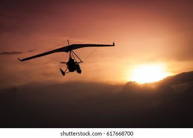 Weight-Shift ultralight aircraft silhouette  in the sunset, above stormy clouds