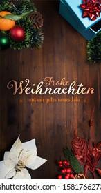 """Frohe Weihnachten und ein gutes neues Jahr"" t.i. Merry Christmas and Happy New Year in German language on a wooden background with decoration Smartphone Vertical orientation view for message app wish"