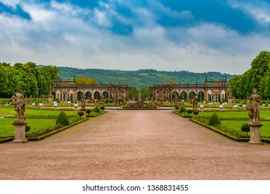Weikersheim, Germany - MAY 2010: The lovely walkway to the Baroque garden of Weikersheim Palace, framed by two statues, is leading to the beautiful Hercules Fountain and the picturesque orangery.