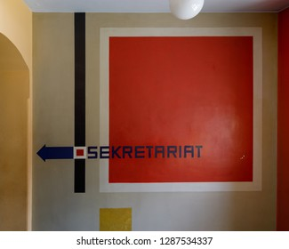 """Weimar, Germany - May 26 2017: Direction sign to the Secretariat in a staircase of the main building of Bauhaus University Weimar (german: """"Bauhaus-Universität Weimar"""")"""