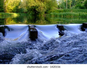 Weir with glassy water reflecting beautiful evening sky II