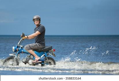Weird biker. Strange biker on a moped driving along the seashore.