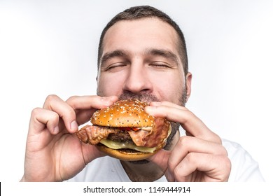 Weird and bizarre man is eating fat and juicy hamburger. It is not a healthy food but the guy likes it very much. His face is very emotional. Isolated on white background.