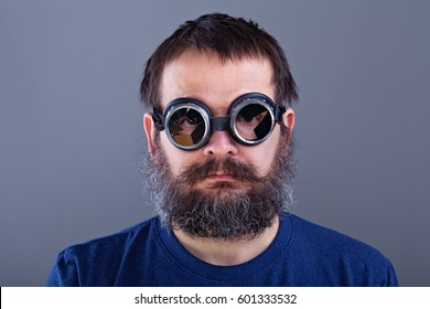 Weird guy with matted hair and large beard wearing broken welding goggles