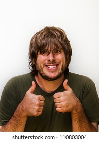 Weird looking guy giving the thumbs up with a big cheesy smile against a white background. Little bit of copyspace above person.
