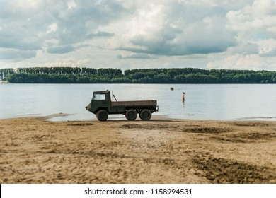 Weird vehicle on the shore/Three axle vehicle parked on the island beach Danube  shore with a person approaching from the water and a distant motorboat.