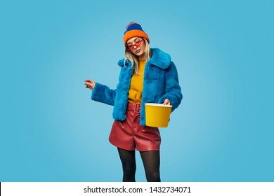 Weird young female in colorful trendy outfit holding bucket of popcorn during showtime against blue background