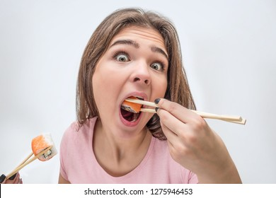 Weird young woman look on camer and put piece of roll in mouth. Another piece hold with chopsticks. Isolated on grey background.
