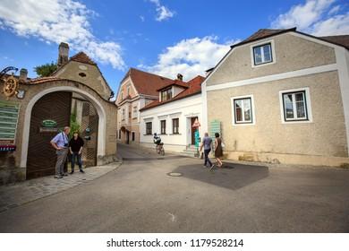 WEISSENKIRCHEN IN DER WACHAU, AUSTRIA - JULY 8, 2018. Old street. Open gate to the heuriger - traditional wine tavern. Weissenkirchen in der Wachau, district of Krems-Land, Lower Austria, Europe.