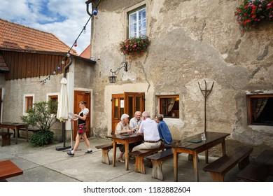 WEISSENKIRCHEN IN DER WACHAU, AUSTRIA - JULY 8, 2018. Elderly people sitting at a table in a street restaurant. Weissenkirchen in der Wachau, district of Krems-Land, Lower Austria, Europe.