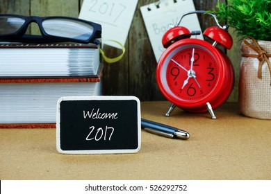 WELCOME 2017 inscription written on chalkboard. Red alarm clock, books, spectacle, notes at background.