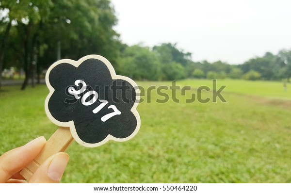 welcome 2017 text on cloud shape chalkboard, park background