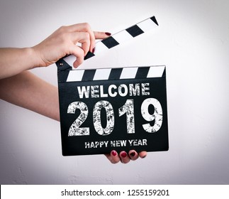 Welcome 2019 Happy New Year. Female hands holding movie clapper