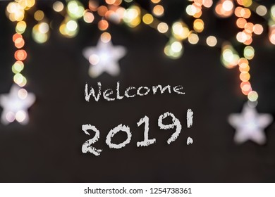 Welcome 2019 text in a black background with lights and stars