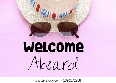 Welcome aboard text. top view of sunglasses, straw hat, flip flops and inscription welcome aboard on pink background