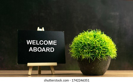 WELCOME ABOARD words on black board with green grass, conceptual