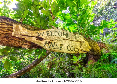 Welcome to Anse Coco sign in tropical jungle. Anse Cocos in La Digue Island, Seychelles is a popular beautiful beach can be reached with a trek starting from Grand Anse and passing through Petite Anse