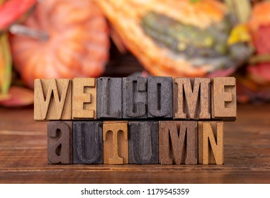 Welcome Autumn message written in wooden block letters with a fall background theme