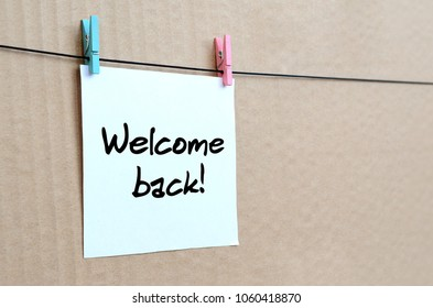 Welcome back! Note is written on a white sticker that hangs with a clothespin on a rope on a background of brown cardboard